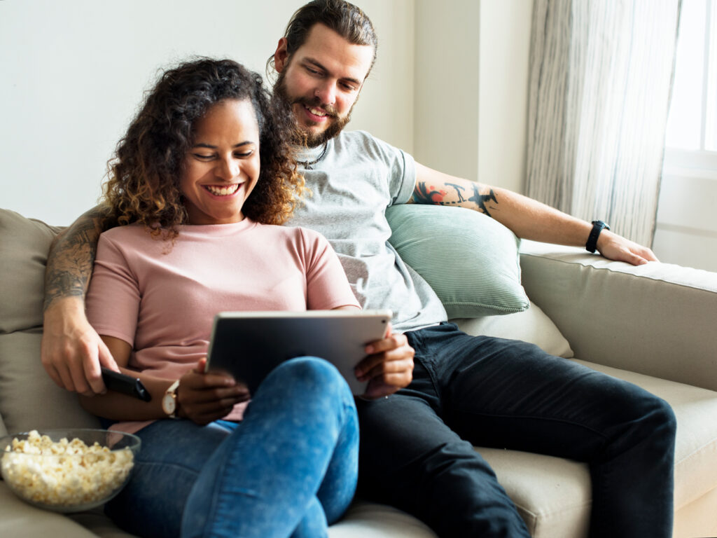 couple at home relaxing on couch looking at a tablet